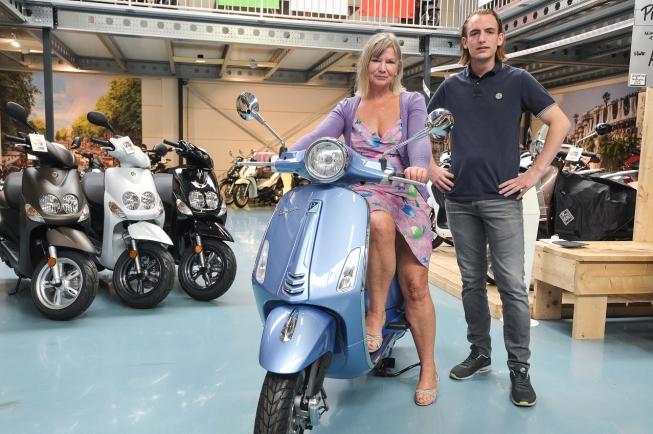 Prijswinnaar neemt scooter in ontvangst