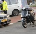 Botsing auto en scooter op rotonde